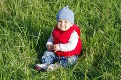 11个月的可爱的婴孩年龄在红色背心的在草 库存图片
