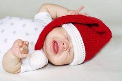 2个月的哭泣的婴孩年龄在一个新年的帽子的 库存图片