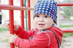 10个月的微笑的婴孩年龄在操场的 免版税图库摄影