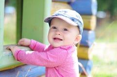 10个月的愉快的微笑的婴孩年龄在操场的在夏天 免版税库存图片
