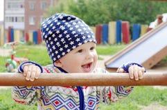 10个月的愉快的婴孩年龄在操场的 图库摄影