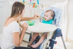 10个月的被定调子的图象坐在高脚椅子在客厅和吃粥的男婴 免版税库存照片