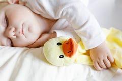 6个月的逗人喜爱的可爱的女婴睡觉平安在床上 免版税库存照片