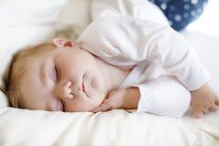 6个月的逗人喜爱的可爱的女婴睡觉平安在床上 库存图片
