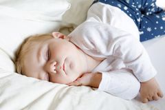 6个月的逗人喜爱的可爱的女婴睡觉平安在床上 图库摄影