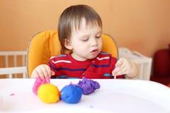 18个月的婴孩年龄画象与彩色塑泥的在家 库存照片