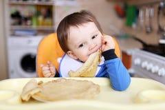 18个月婴孩吃薄煎饼 库存照片