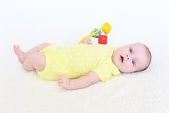 2个月画象使用与吵闹声的女婴 免版税库存图片