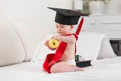 10个月画象毕业盖帽和丝带的男婴 免版税图库摄影