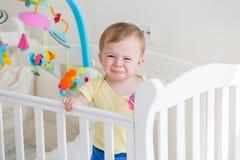 10个月Portriat站立在轻便小床和哭泣的男婴 免版税库存照片
