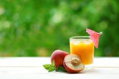 整个桃子和与一杯的一个一半汁液 库存照片