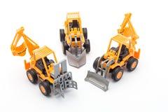 3个桔子拖拉机玩具 免版税库存照片
