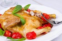 整个烤鸡用蕃茄樱桃、绿色蓬蒿和大蒜 库存照片