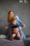 3个照相机长沙发系列女孩查找关于坐的母亲橙色纵向他们那里 年轻三口之家人 免版税库存图片