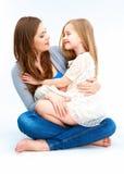 3个照相机长沙发系列女孩查找关于坐的母亲橙色纵向他们那里 母亲huging的女儿 免版税库存图片