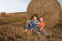 2个男孩在领域的一个干草堆 库存照片
