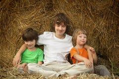 3个男孩在领域的一个干草堆 免版税库存照片