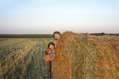 3个男孩在领域的一个干草堆 免版税库存图片