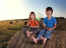 2个男孩在领域的一个干草堆 免版税库存照片