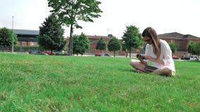 4个白色女衬衫、黄色短裤和太阳镜的k俏丽的深色的棕色头发女孩,坐绿草在 影视素材