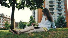 4个白色女衬衫、黄色短裤和太阳镜的k俏丽的深色的棕色头发女孩,坐绿草在 股票录像