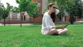 4个白色女衬衫、黄色短裤和太阳镜的k俏丽的深色的棕色头发女孩,坐绿草在 股票视频