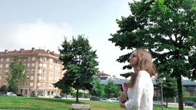 4个白色女衬衫、黄色短裤和太阳镜的k俏丽的深色的棕色头发女孩,走和微笑在绿色 影视素材