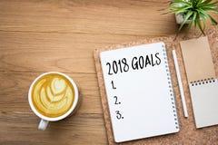 2018个目标在与办公室辅助部件和咖啡杯的笔记薄发短信 库存照片
