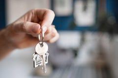 100个票据概念美元房子做抵押 人递对负关键与房子被塑造的keychain 现代轻的大厅内部 房地产,移动的家 免版税图库摄影