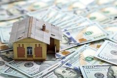 100个票据概念美元房子做抵押 安置货币 在堆的微型房子模型 图库摄影