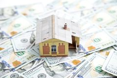 100个票据概念美元房子做抵押 安置货币 在堆的微型房子模型 免版税库存照片
