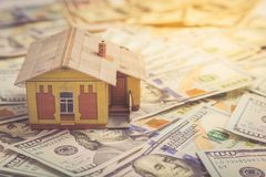100个票据概念美元房子做抵押 安置货币 在堆的微型房子模型 免版税图库摄影