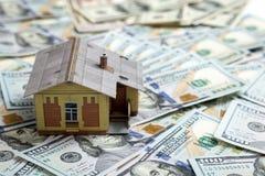 100个票据概念美元房子做抵押 安置货币 在堆的微型房子模型 库存图片