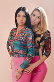 2个美丽的白肤金发和深色的性感的少妇女朋友或姐妹获得一起站立的乐趣在桃红色皮革礼服 免版税库存照片