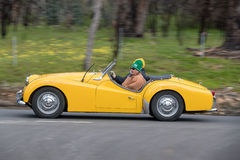 1959个胜利TR3A敞篷车驾驶在乡下公路 免版税图库摄影