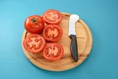 整个蕃茄和一半与蕃茄刀子 库存图片