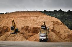 10个轮子卡车装载木片在准备好的料堆装载到出口的船 纸和生物量产业 图库摄影