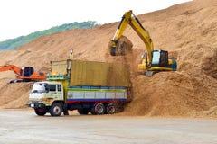 10个轮子卡车装载木片在准备好的料堆装载到出口的船 纸和生物量产业 免版税库存图片
