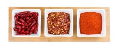整个辣椒、辣椒剥落和卡宴粉末在白色背景 库存照片