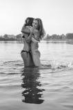 2个年轻美丽的最佳的女朋友黑白色摄影比基尼泳装的获得放松的乐趣在水中在夏日 图库摄影