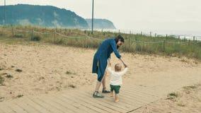 4个k美丽的女孩,走和花费与她逗人喜爱的矮小的婴孩的母亲时间,在Cantabrian海岸中,在 影视素材
