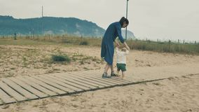 4个k beautifull女孩,走和花费与她逗人喜爱的矮小的婴孩的母亲时间,在Cantabrian海岸中,在 影视素材