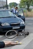 击中一个女性骑自行车的人的司机 库存照片