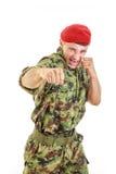 击中与拳头的制服和盖帽的恼怒的军事战士 免版税库存照片