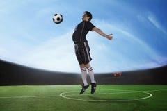 击中与他的胸口的足球运动员球在体育场,天时间内 免版税库存照片
