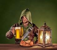 中世纪人在一个小酒馆用在葡萄酒背景的啤酒 库存照片