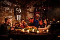 中世纪人民在古老城堡厨房内部吃并且喝 免版税库存照片