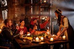 中世纪人民在古老城堡厨房内部吃并且喝 免版税图库摄影