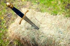 中世纪剑在堆黏附了干草 免版税图库摄影