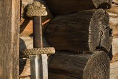 中世纪北欧海盗剑对木墙壁 库存照片